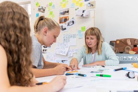 Auf dem Foto sind 3 Frauen zus ehen die an einem Schreibtisch sitzen und über eine Entwurf diskustieren. Im Hintergrund ist eine große Pinwand an der verschiedene Entwürfe hängen.