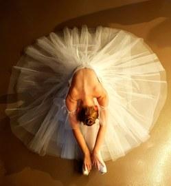 Das Foto zeigt eine Aufnahme einer Ballettänzerin von oben, die mit weit aufgefächertem Balletrock mit nach vorn gebeugten Oberkörper auf dem Boden sitzt.