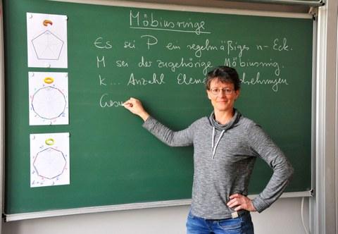Das Foto zeigt eine Frau (Dr. Antje Noack) vor einer grünen Schultafel, an die sie einen Satz über Möbiusringe geschrieben hat.