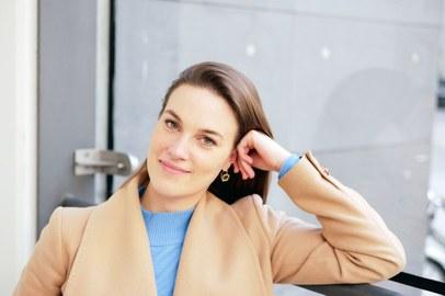 Das Foto zeigt eine junge Frau vor einer Glasfront, ihr Ellenbogen ist aufgestützt.