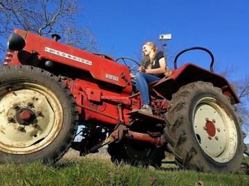 Das Foto zeigt eine junge Frau auf einem roten Traktor.