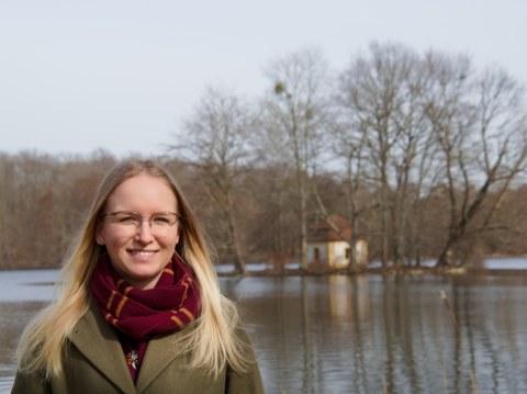 Das Foto zeigt Henriette Heinrich vor einem Teich. Im Hintergrund ist ein kleines Häuschen auf einer kleinen Insel zu sehen.
