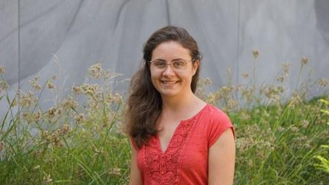 Das Bild zeigt eine junge Frau vor einer blühenden Wiese.