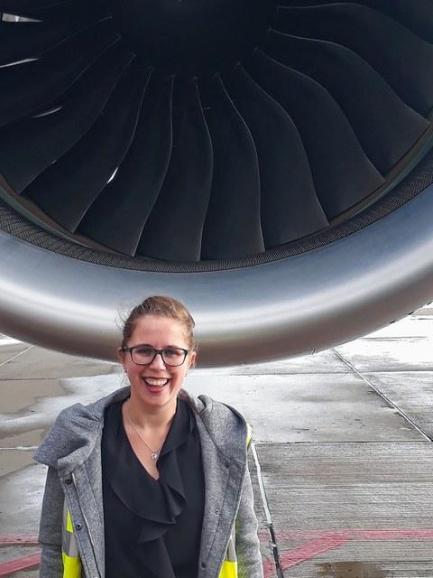 Das Bild zeigt eine Frau vor einem riesigen Flugzeugtriebwerk.