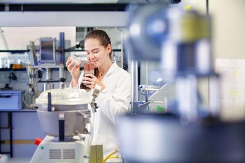 Das foto zeigt eine junge Frau im Labor, die ein Gefäß geöffnet hat und daran riecht.