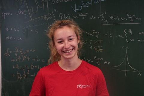 Das Bild zeigt eine junge blonde Frau vor einer grünen  Tafel an der viele verschiedene mathematische Gleichungen und Formeln geschrieben sind.