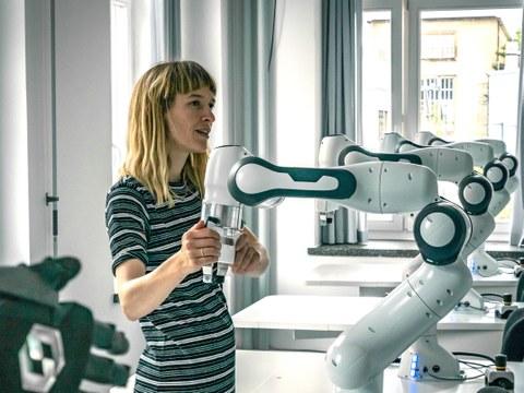 Auf dem Bild ist eine Frau zu sehen die einen Roboterarm bedient. Im Hintergrund sind weitere Roboterarme zu sehen.