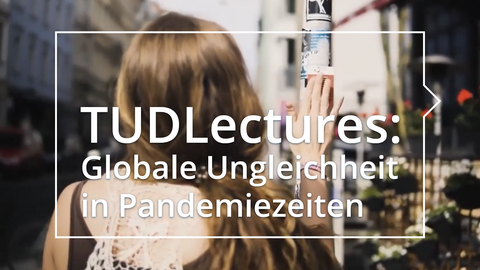 Das Bild zeigt einen Ausschnitt aus dem Video der Hochschulgruppe Medinetz Dresden. Man sieht eine Frau von hinten, die einen Aufkleber an einen Straßenpfosten klebt.