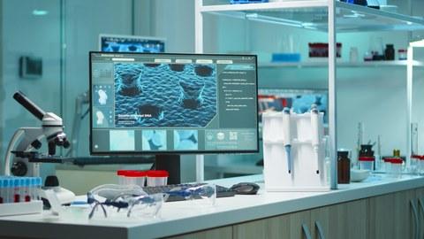 Laborinterieur mit Mikroskop und Monitor im Vordergrund