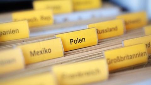 """Foto von Akten, die mit Ländernamen wie """"Polen"""", """"Russland"""", """"Mexico"""", etc. beschriftet sind"""