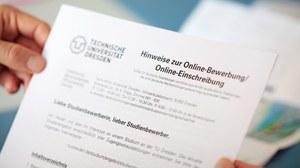"""Foto von zwei Händen, die ein Dokument halten. Darauf ist neben einem Logo der TU Dresden zu lesen: """"Hinweise zur online Bewerbung"""""""