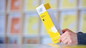 Foto zweier Hände, die einen aufgeschlagenen Gelben Flyer halten, auf dem das Logo der TU Dresden zu sehen ist