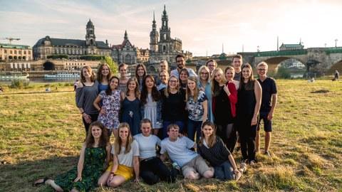 Foto einer Gruppe Studierender auf den Elbwiesen, im Hintergrund die Dresdener Altstadt