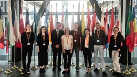 Foto einiger IB-Studierenden vor den Flaggen der EU-Mitgliedsstaaten beim Europäischen Gerichtshof