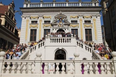 Frontales Foto eines barocken Gebäudes. Auf der Treppe zum Eingang befinden sich etwa einhundert Studierende
