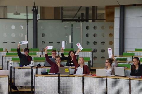 Studierende sitzen in einem Konferezsaal und halten Abstimmungskarten in die Höhe..