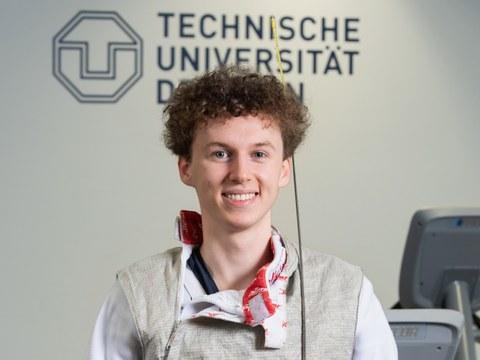 Portraitfoto von Laurenz Rieger in Fechtkleidung mit Florett