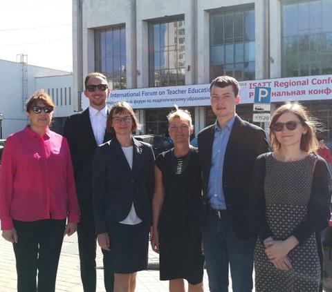 """Foto einer Gruppe von 6 Personen, die vor einem Gebäude stehen. An dem Gebäude ist ein Banner mit Wörtern in Englisch und Russisch angebracht. """"International Forum on Teacher Education"""" ist unter anderem zu lesen."""