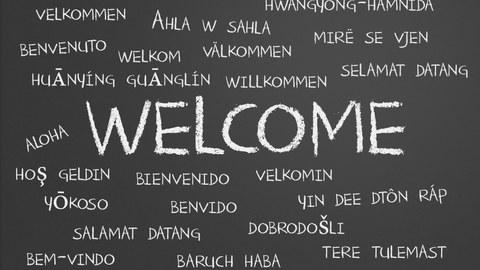 """Foto einer Tafel, auf der das Wort """"Willkommen"""" in vielen verschiedenen Sprachen steht"""