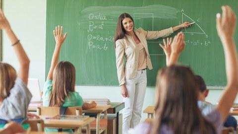 Das Foto zeigt eine Grundschulklasse im Mathematikunterricht. Die Lehrerin zeigt mit ihrer Kreide auf eine Seite eines Dreiecks, welches an die Tafel gemalt wurde. Alle Lernenden melden sich.