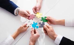 Sechs Hände verschiedener Personen halten sechs verschieden farbige Puzzleteile als Kreis in die Mitte.