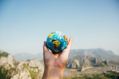 Foto mit einer Hand im Vordergrund, die einen kleinen Ball in Gestalt einer Weltkugel hochhält. Im Hintergrund ist eine Landschaft mit Bergen.