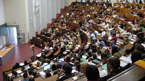 Das Foto zeigt die Bankreihen eines großen Hörsaals. Fast alle Plätze sind belegt.