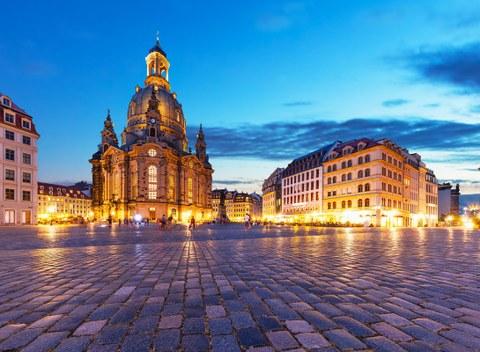 Foto des Dresdner Neumarktes mit der Frauenkirche. Es ist Abend, einige Menschen sind auf dem Neumarkt zu Fuß unterwegs.