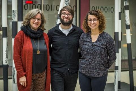 Bild einer Gruppe von 3 Personen, die in die Kamera lächeln