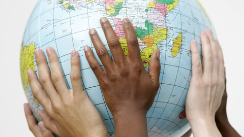 Bild von 6 Händen, die gemeinsam einen Globus hochhalten