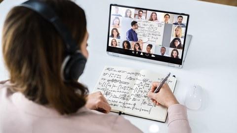 Das Foto zeigt eine Person, die Notizen in ein Heft schreibt, während sie auf ein Tablet schaut.