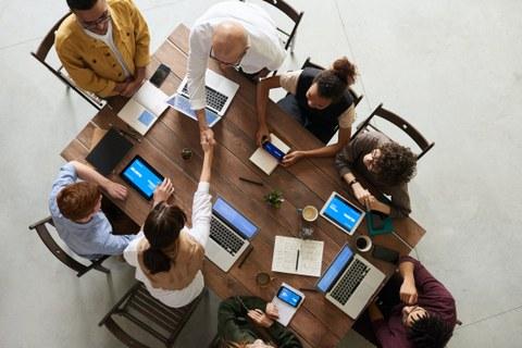 Foto einer Gruppe von 8 Personen in Vogelperspektive. Die Personen sitzen um einen Holztisch und arbeiten an mobilen Endgeräten, Laptops oder mit Notizbüchern. Eine Frau und ein Mann reichen sich über den Tisch hinweg die Hand.