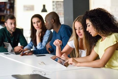 Bild einer Gruppe von 5 Personen, die an einem Tisch sitzen und miteinander arbeiten
