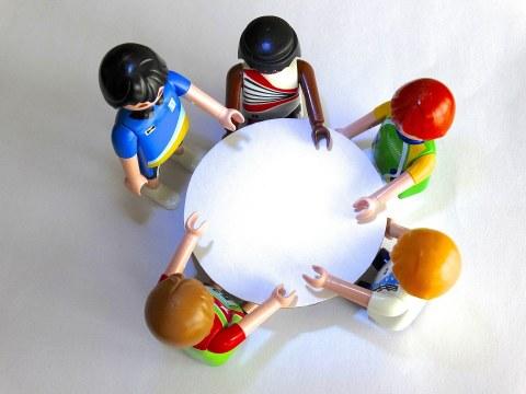 Auf dem Foto aus der Vogelperspektive sind ein runder Tisch und fünf diverse Playmobil-Figuren zu sehen, die um den Tisch herum stehen und sich unterhalten.