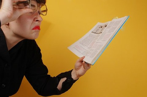 Bild einer Frau, die mit skeptischem Gesichtsausdruck in einem Buch liest.