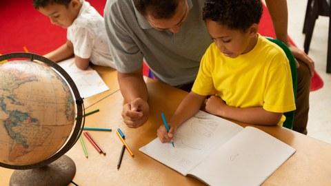Das Foto zeigt zwei Kinder, die an einem Tisch sitzen und mit Farbstiften etwas in ein leeres Heft malen. Hinter dem einen Kind kniet ein Mann und schaut dem Kind über die Schulter. Auf dem Tisch befindet sich ebenfalls ein Globus.