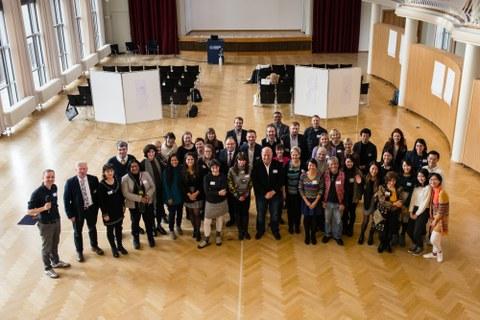 Bild von einer Gruppe aus über 20 Personen, die in einem ansonsten leeren Saal mit Stuhlreihen und einer Bühne stehen und in die Kamera lächeln.