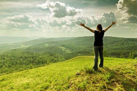 Eine junge Frau steht glücklich auf einem Berg und hebt die Arme