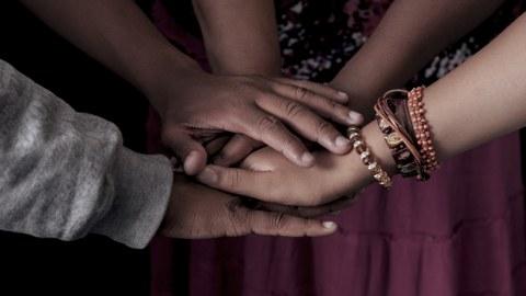 Das Foto zeigt die Hände mehrerer Personen. Sie stehen im Kreis und haben die Hände übereinander gelegt. Eine Person trägt Armschmuck.