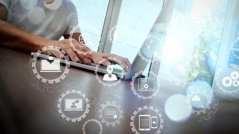 Foto: Ein Mann sitzt am Laptop an einem Tisch. Im Vordergrund sind Symbole, die für Technik und Studium stehen.