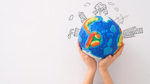 Grafik mit einer Erde aus Knete, die von zwei Händen in die Höhe gehalten wird.