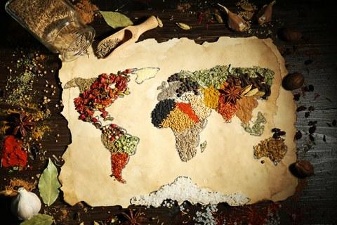 Das Foto zeigt einen Tisch mit vielen Gewürzen. In der Mitte des Tisches liegt ein Stück altes Papier mit den Umrissen einer Weltkarte. Die einzelnen Kontinente sind mit unterschiedlichen Gewürzen ausgefüllt.