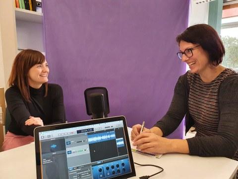 Auf dem Foto sind zwei Frauen zu sehen, die an einem Tisch sitzen, sich anschauen und lachen. Auf dem Tisch im Vordergrund sind ein Laptop und ein Podcastmikrofon zentral platziert. Im Hintergrund steht eine lila Wand.