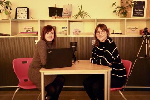 Auf dem Foto sind 2 Frauen zu sehen, die sich an einem Tisch im Lehr-Lern-Raum Inklusion gegenübersitzen. Auf dem Tisch steht ein Laptop und ein Podcastmikrofon. Die beiden Frauen lächeln in die Kamera.