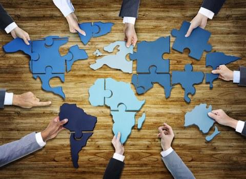 Foto. Auf einem Holzuntergrund liegen Puzzle-Teile, welche die Kontinente der Welt formen. 8 Hände halten jeweils ein Puzzleteil. 2 Hände zeigen auf das Puzzle.