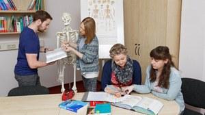 Bild von einem Raum, in dem 4 Personen miteinander lernen. 2 Personen sitzen an einem Tisch und schauen gemeinsam in ein aufgeschlagenes Buch. Die beiden anderen Personen stehen hinter dem Tisch und vor einem Skelett und diskutieren miteinander.