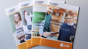 Das Foto zeigt vier Broschüren mit Informationen zu den Lehramtsstudiengängen, die auf einem Tisch aufgefächert sind.