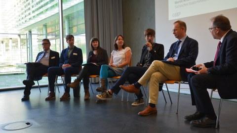 Bild von 7 Personen auf einer TUD-Sylber-Konferenz. Sie sitzen nebeneinander auf Stühlen und reden miteinander.