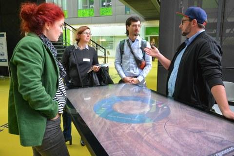 Bild von 4 Personen, die um einen großen Bildschirm stehen. Ein Mann erklärt den anderen 3 Personen etwas.