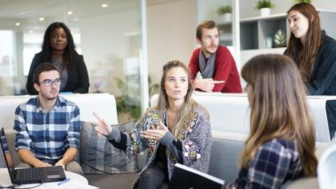 Bild von 6 Personen. 3 Menschen sitzen um einen Tisch auf einer Couch und reden miteinander. Die 3 anderen Personen stehen hinter der Couch und hören zu.